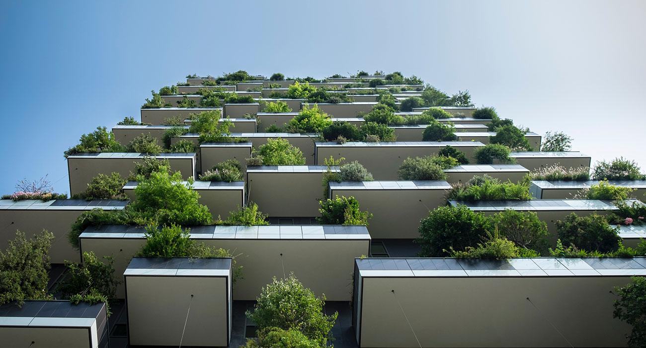 Hochhaus mit Pflanzen auf Balkonen von unten nach oben fotografiert