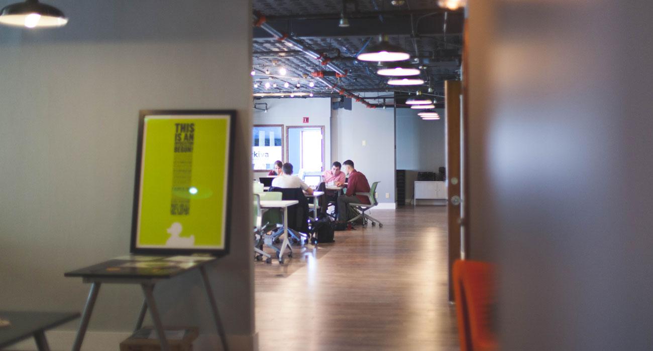 Einblick durch Tür in Konferenzraum, Männer sitzen an Tisch zusammen