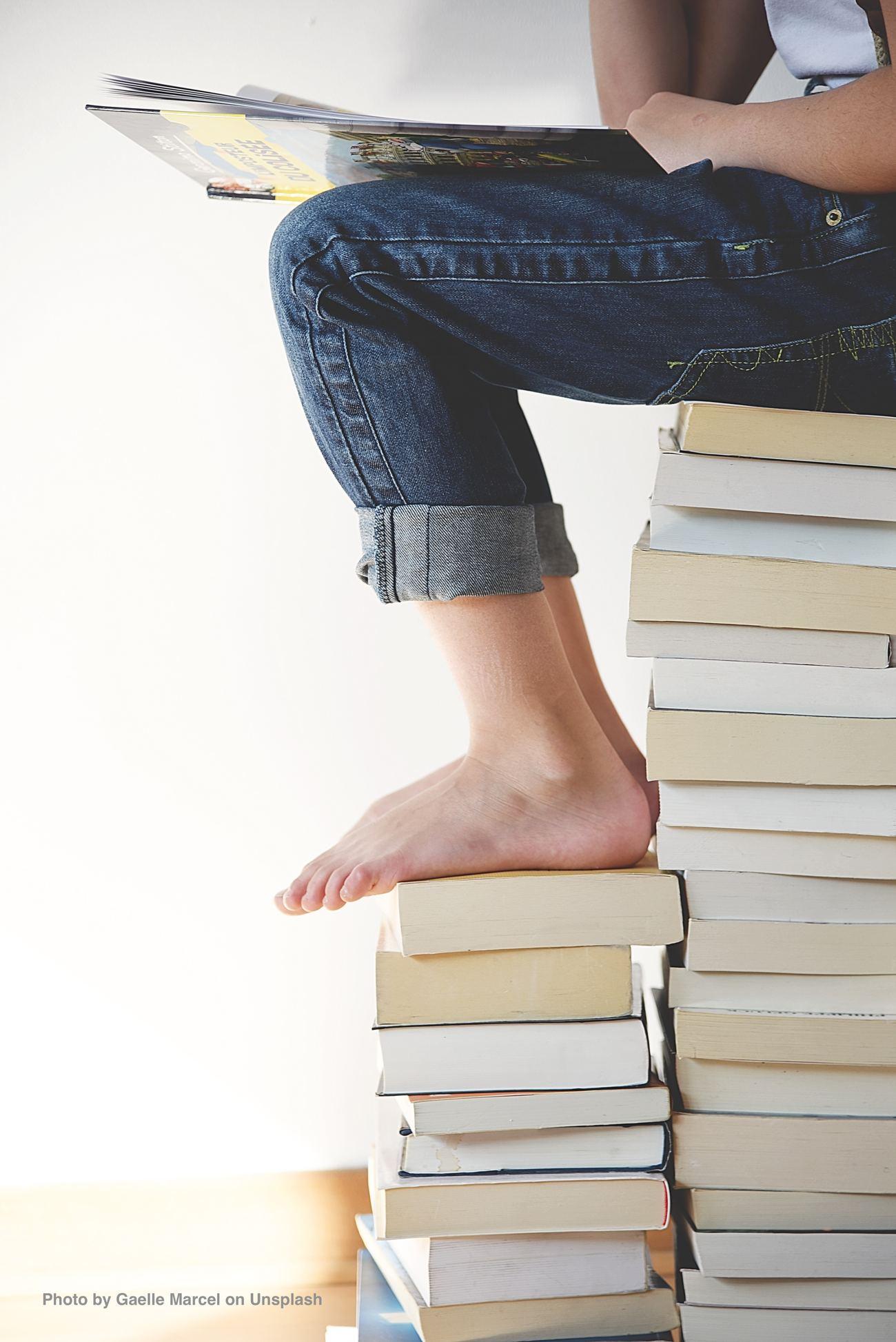 Beine in Jeans und nackte Füße auf Bücherstapel