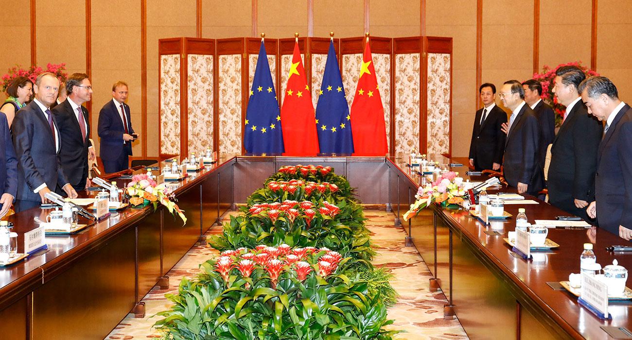 Männer in Anzügen stehen sich gegenüber, im Hintergrund Flaggen