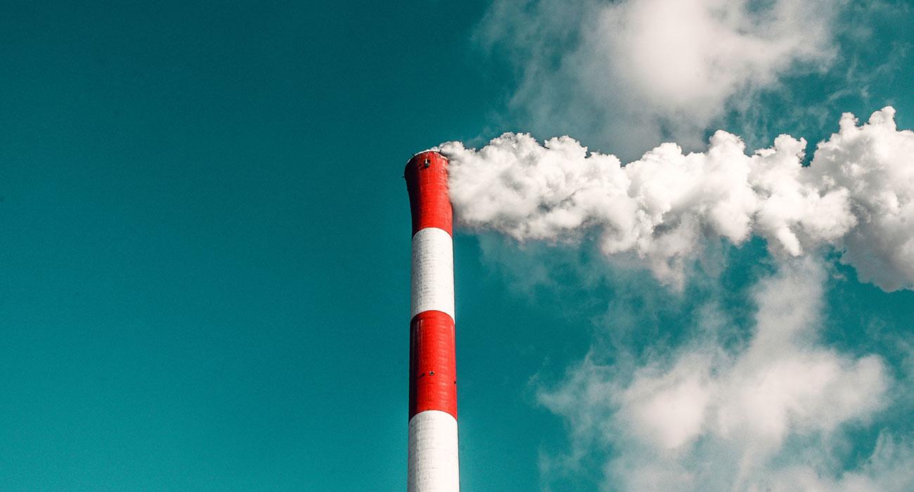 Rot-weisser Schornstein mit Rauch vor blauem Himmel
